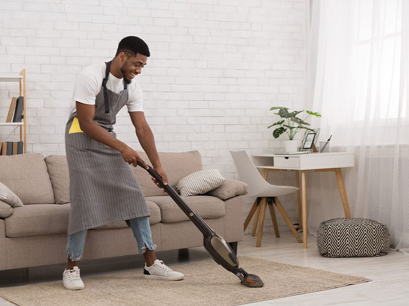 African American man cleaning house with a wireless vacuum