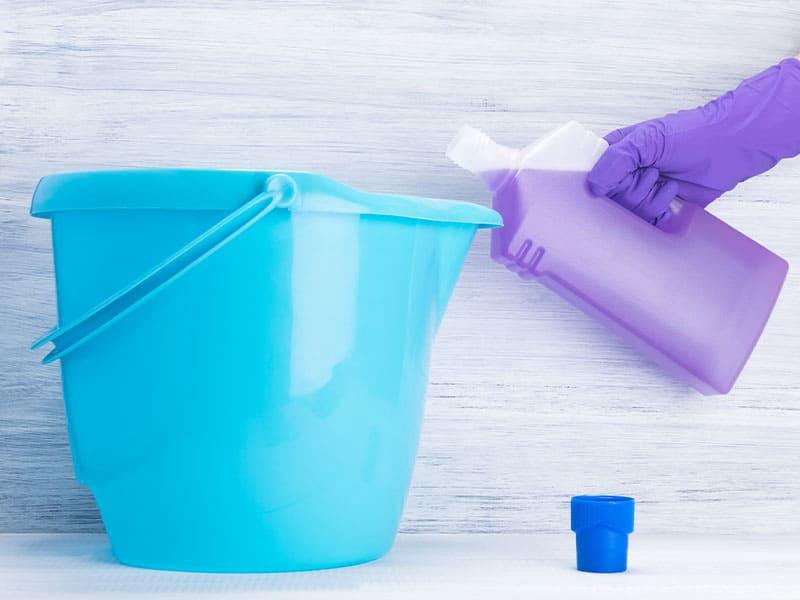 Pour detergent into a blue bucket