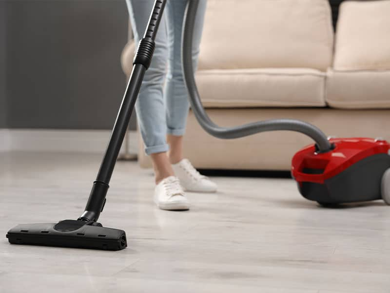 Using a vacuum cleaner at home to pick up dust with ease