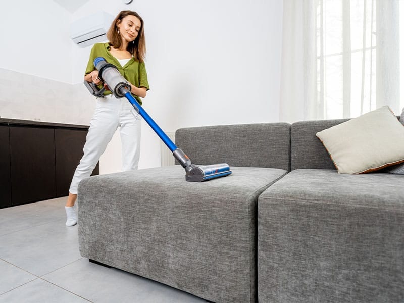 Woman cleaning sofa with a cordless vacuum