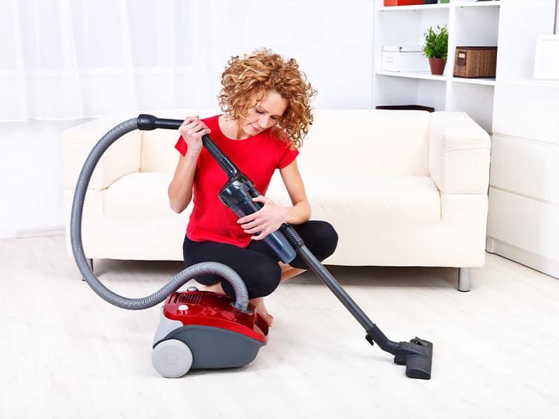 Woman repairing a vacuum cleaner