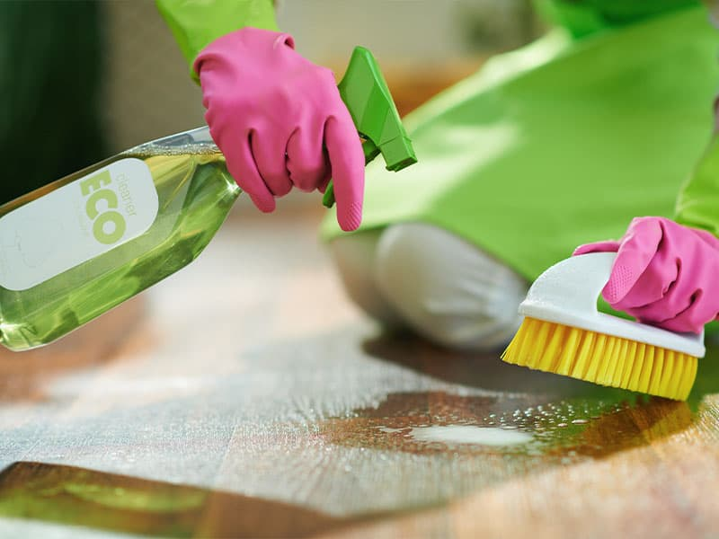 Woman with pink rubber gloves cleaning laminate floor
