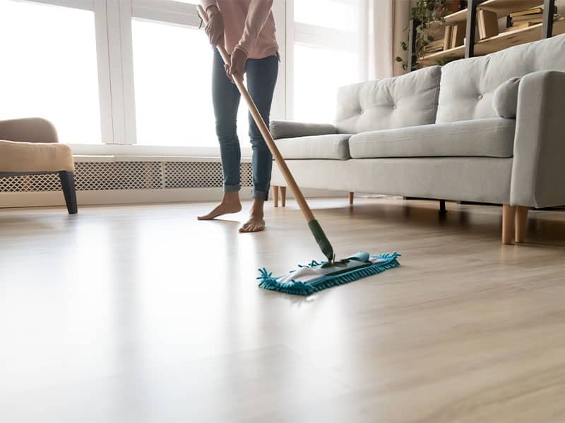 Young woman cleaning laminate floor