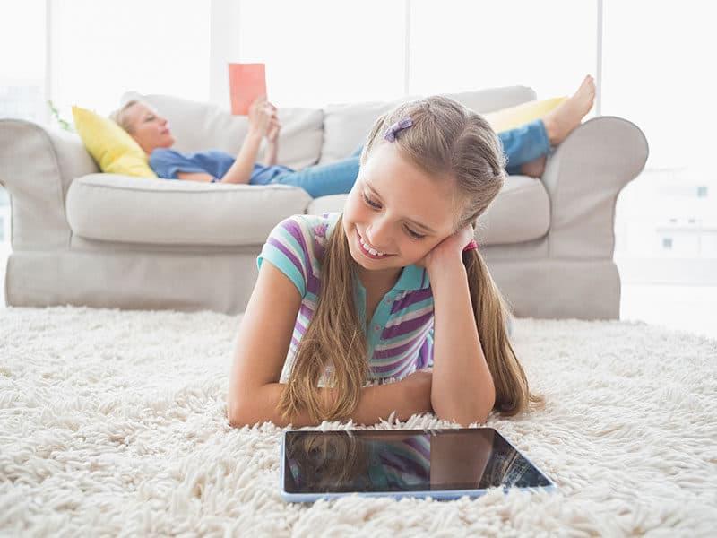 Girl Using Digital Tablet on Carpet