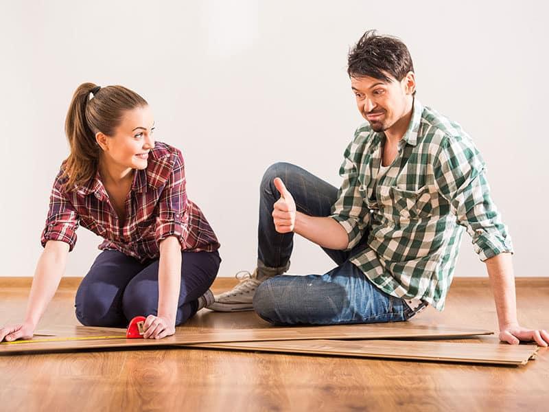 Couple installing laminate flooring