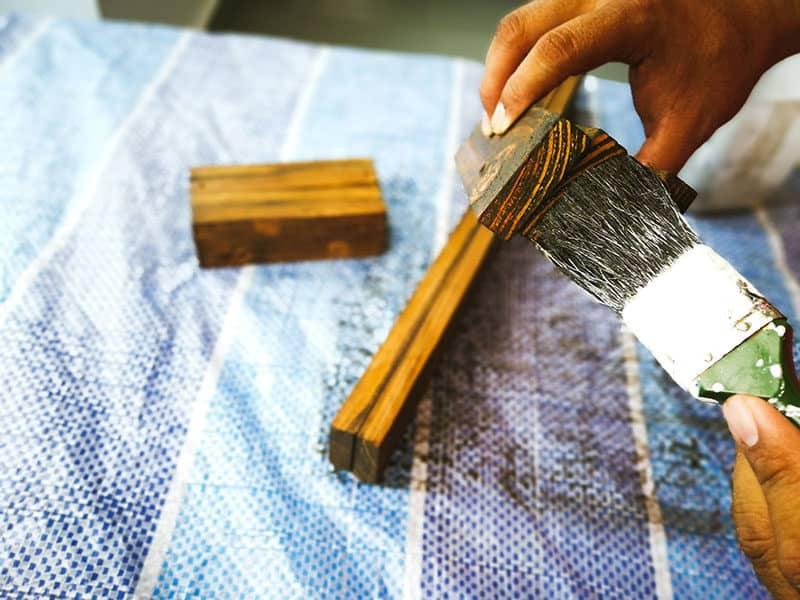 Hand Holding Brush Staining Wood